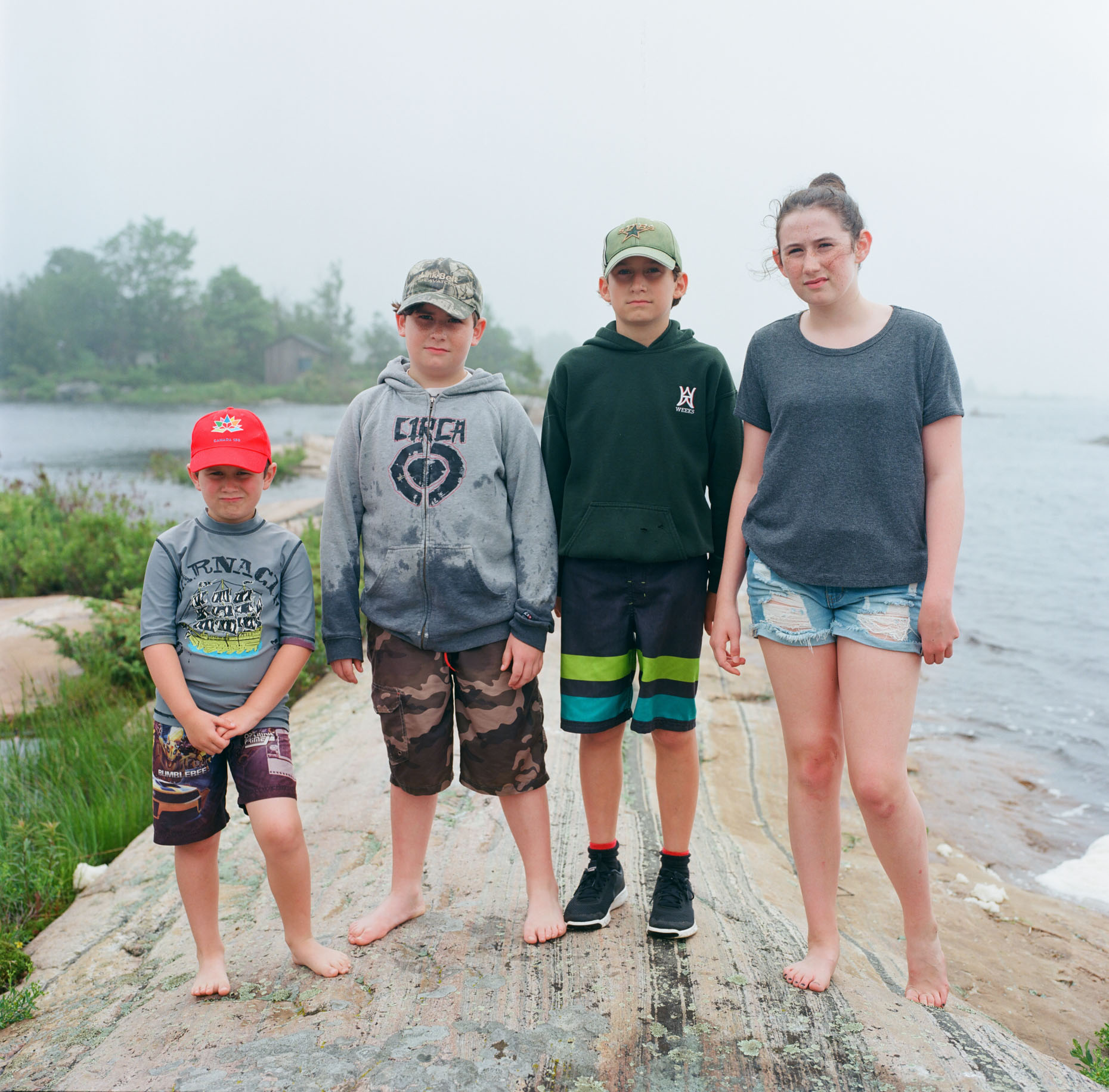 A family of children pose for their portrait on a overcast day in Georgia Lake, Canada