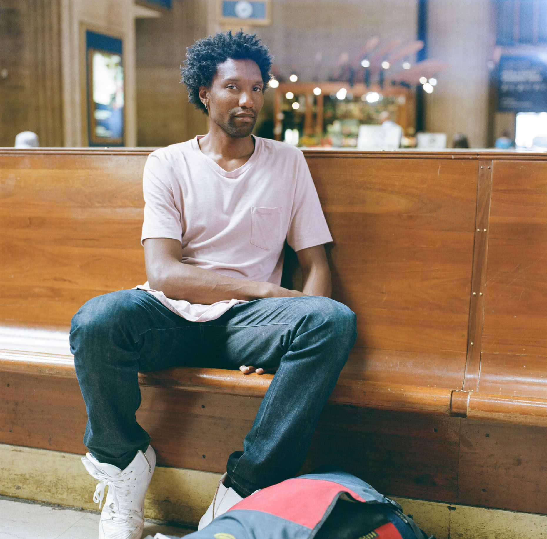 A color portrait of Ifanyi Bell waiting for his train in Philadelphia, USA.