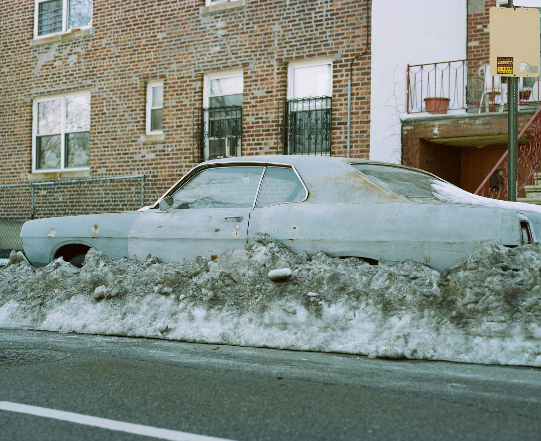 A vintage car sits surrounded by old and dirty snow in Brooklyn, New York