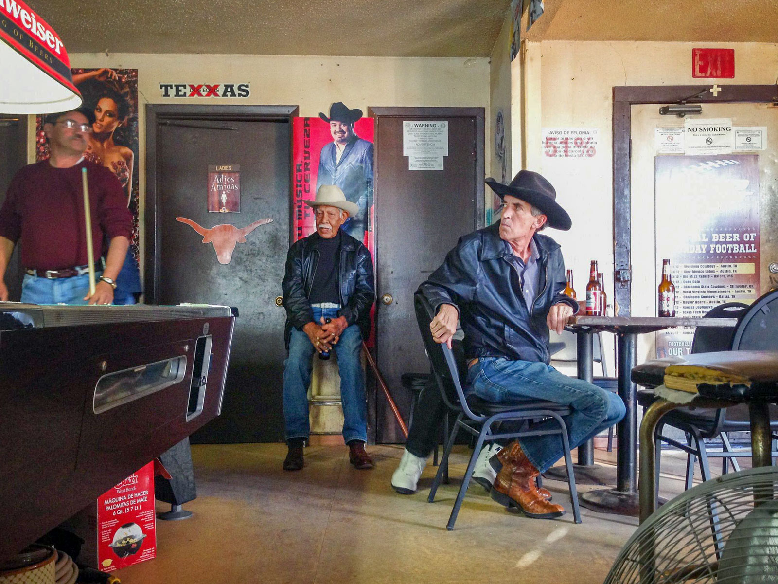 Cowboys relax and play pool in a bar in Austin, Texas, USA