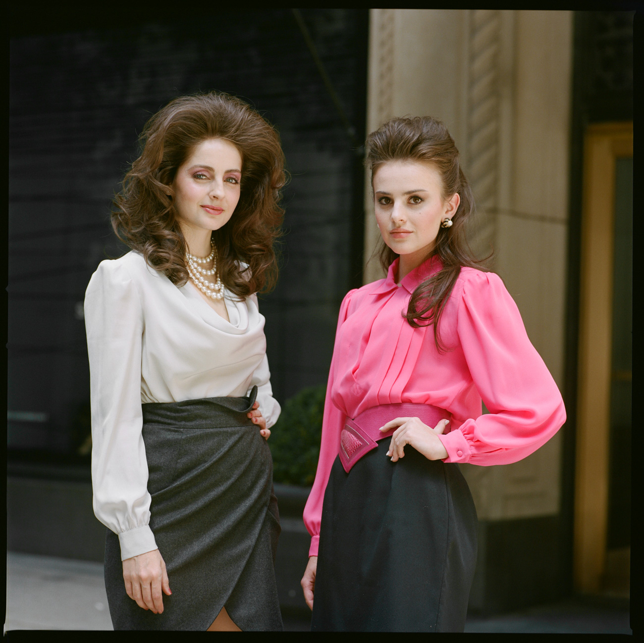 Two ladies take a break outide in midtown from filming an 80s theater production.