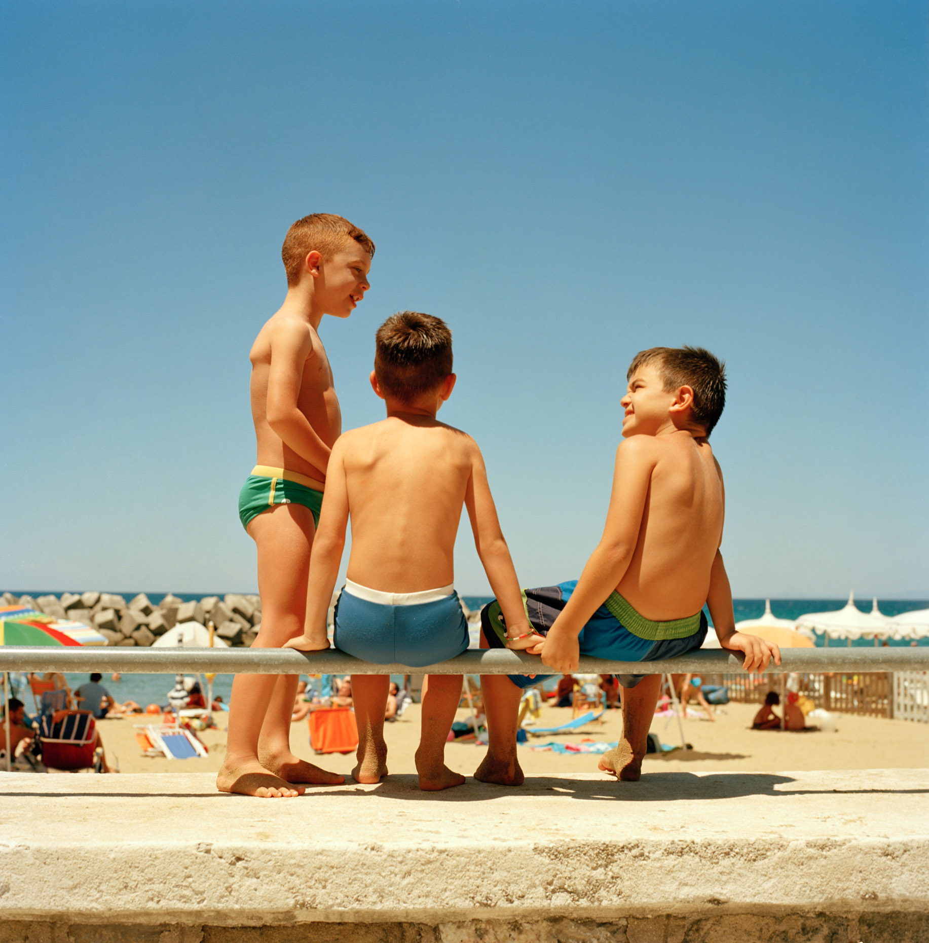 Children talk on the Sea wall in Santa Maria di Castellabate, Italy