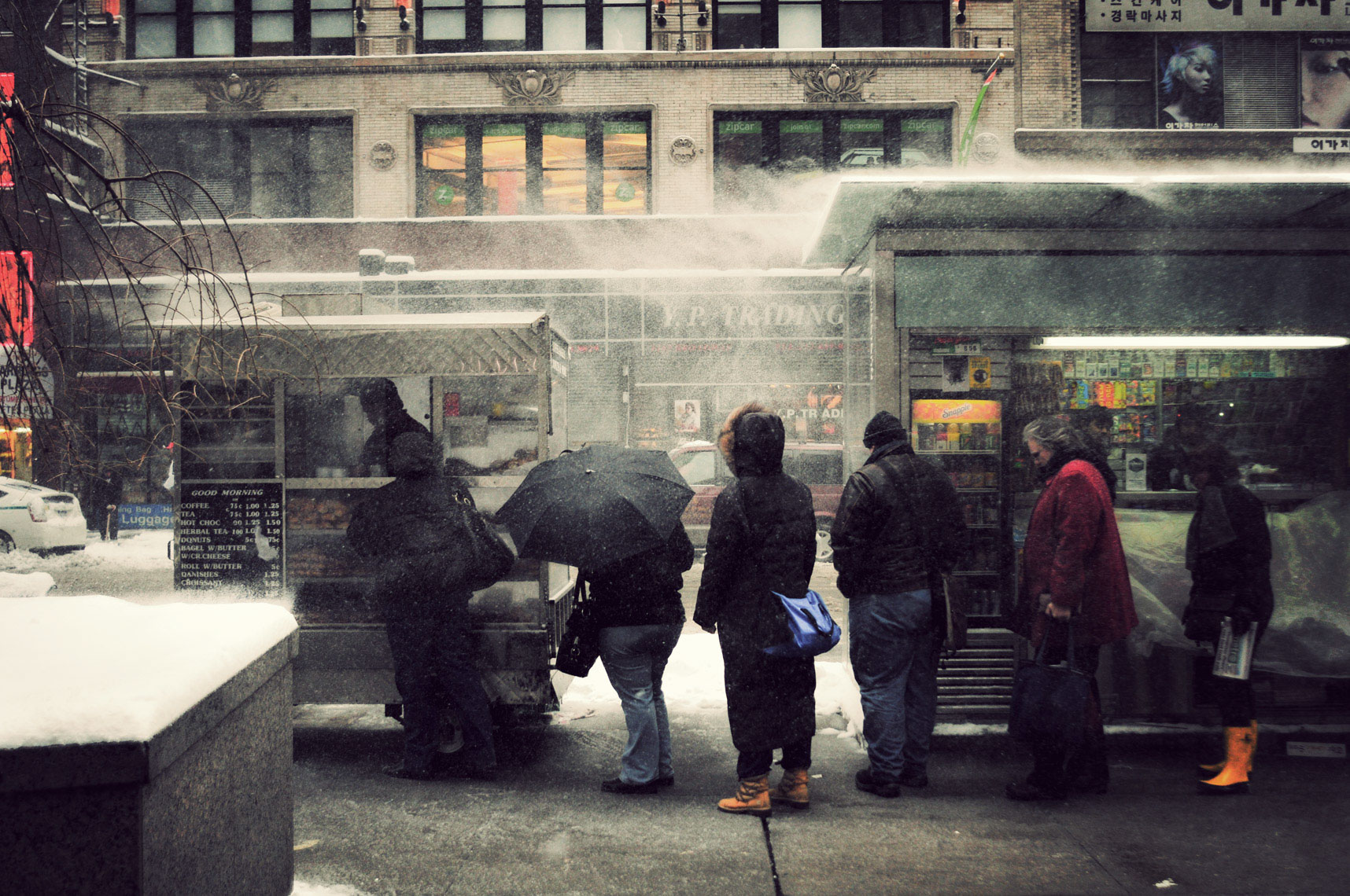 People wait in line for their morning coffee amid miserable weather at 32nd Street, New York City.