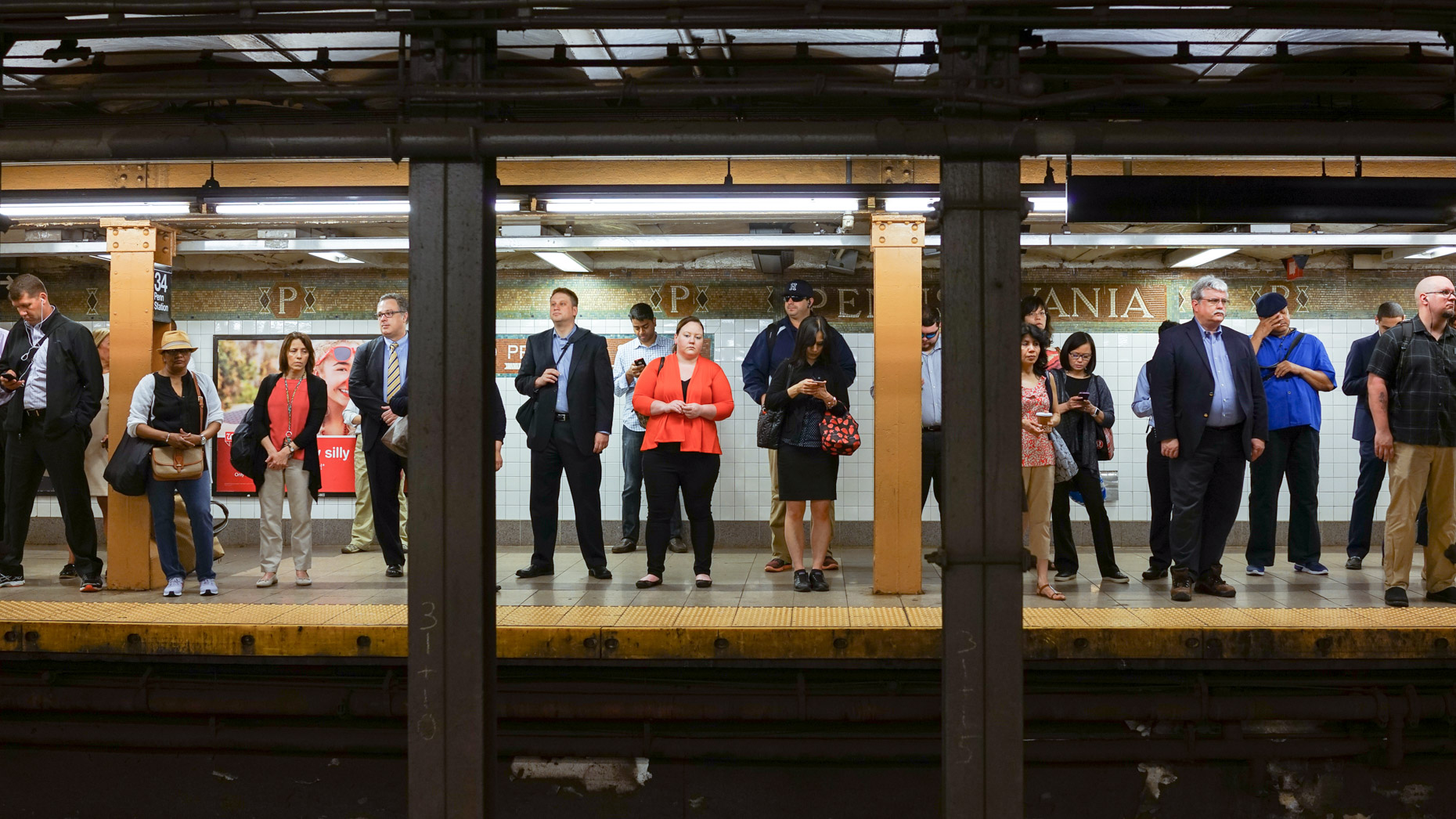 Commuters wait for a subway at one of New York