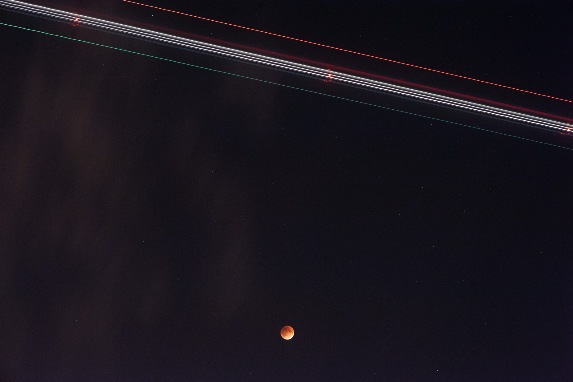 A long exposure of an airplane passes over the blood red moon eclipse of  leaving light trails in it