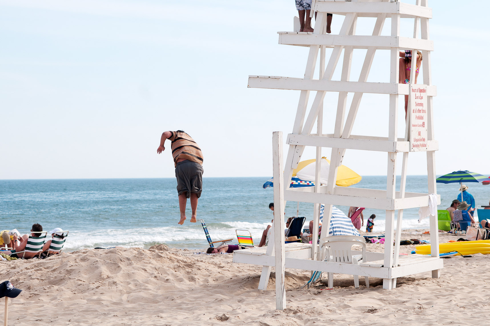 Child leaps off the lifeguard chair, Hamptons, Long Island, New York
