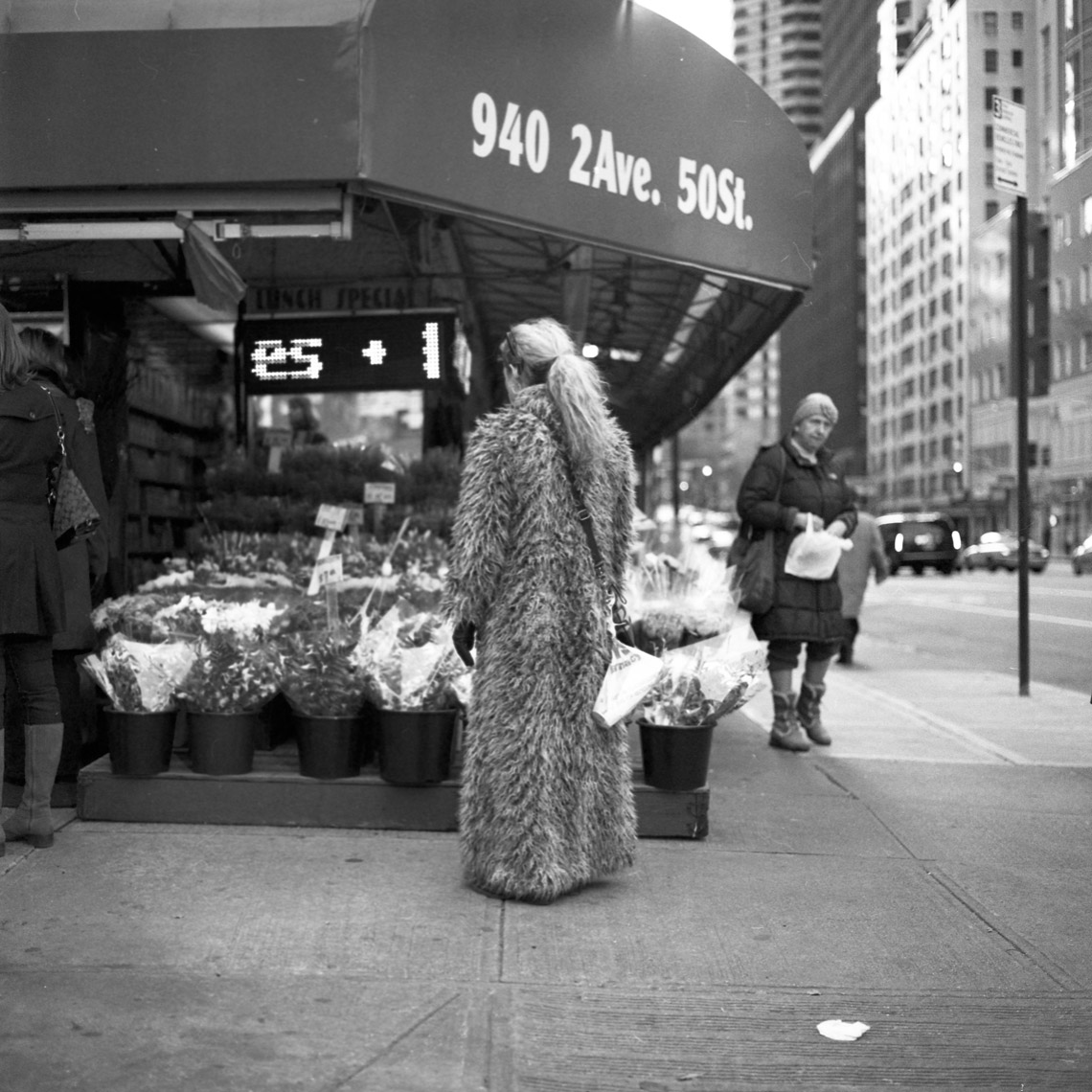 A woman in a fur-coat stops to look at flowers in the upper east side in New York City