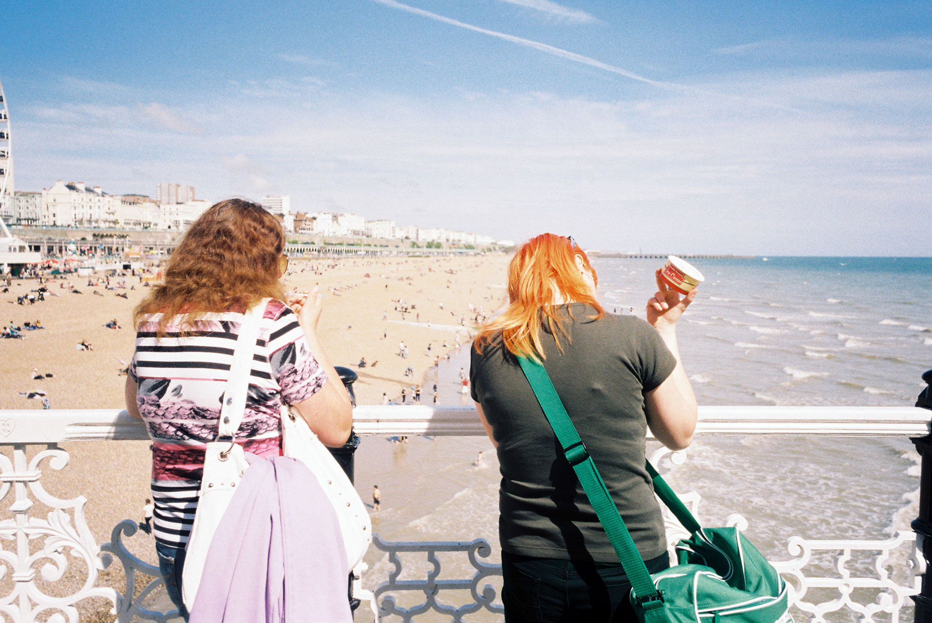 Two women eat Ice Creams on Brighton pier in England.