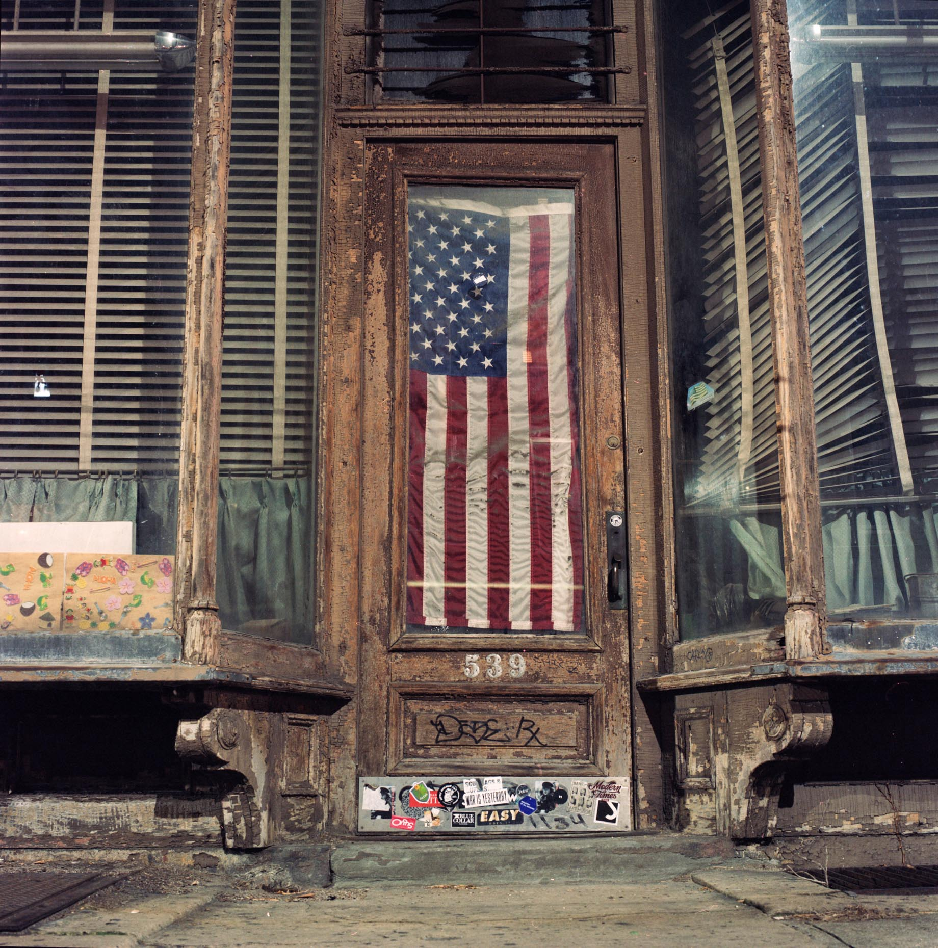 An American flag hangs in the doorway of an abandoned store on Driggs Ave in Brooklyn