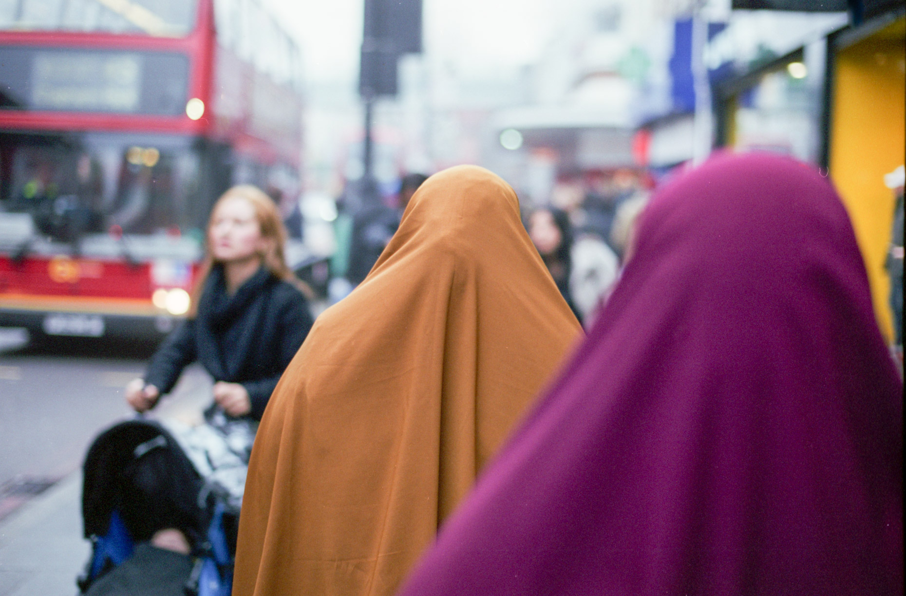 Two muslim women walk through the crowded streets of Brixton, London on a December afternoon.