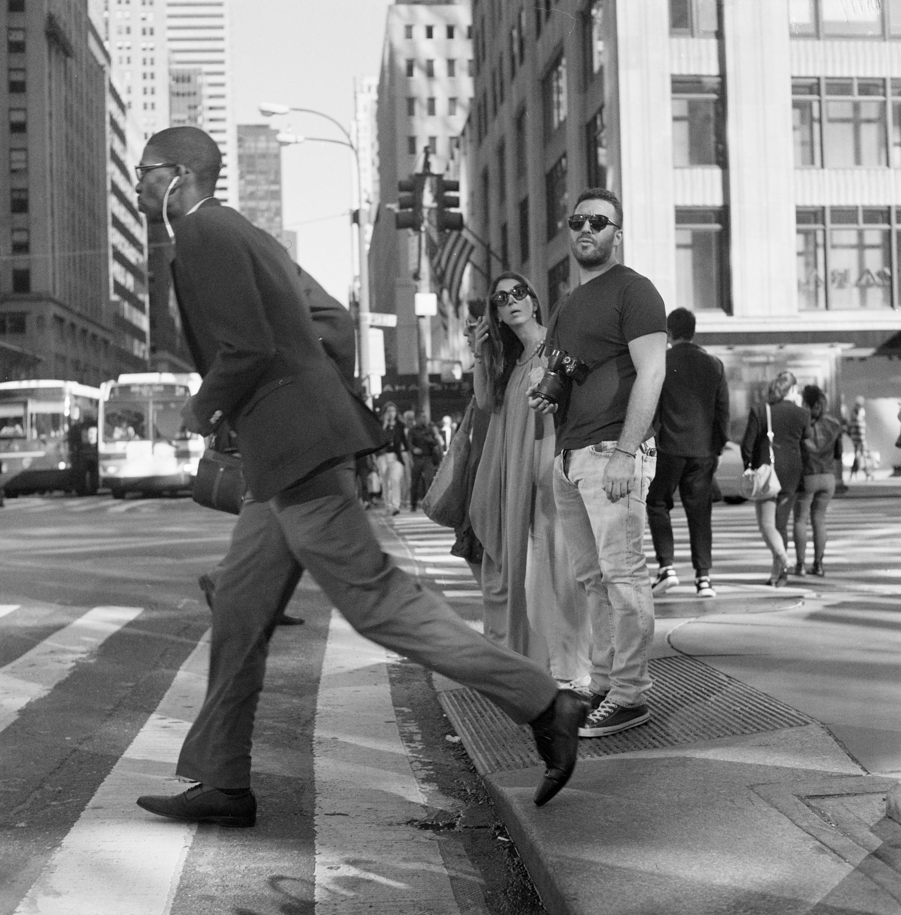 A tall man runs across busy New York Street in Midtown Manhattan, New York City.