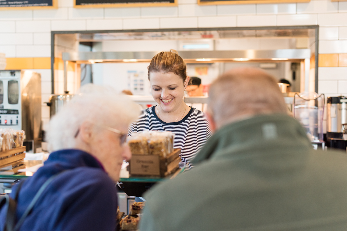 An elderly couple order delicious food from a female employee at Friska Restaurants, Bristol, UK.