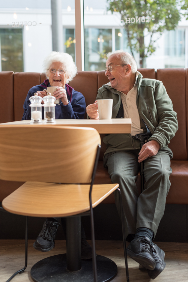 A cute elderly couple laugh and joke while sipping on their coffee and tea at the Bristol City Center, Friska Restaurant.