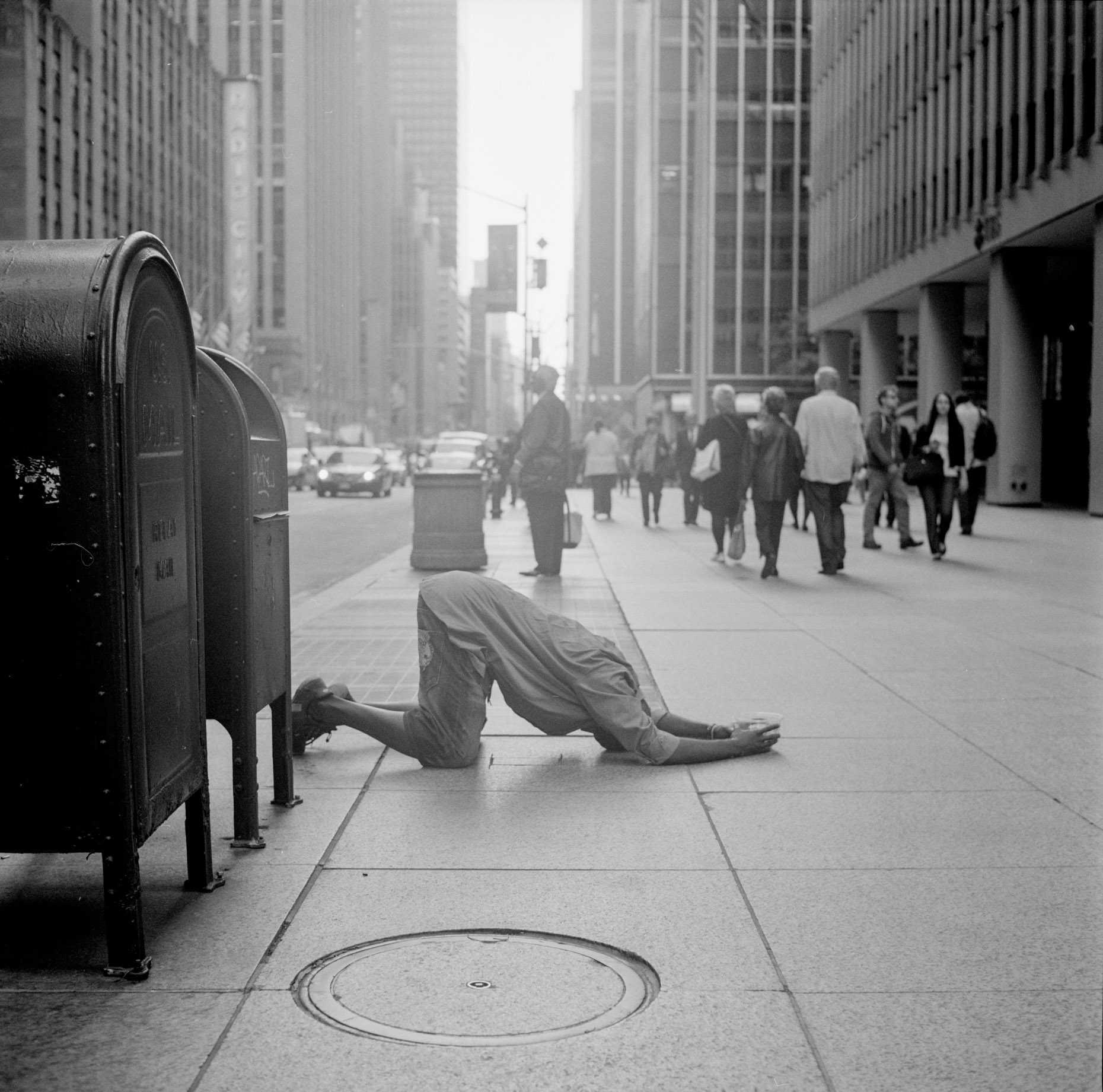 A black and white street image of a man praying in the streets of Midtown Manhattan, New York City.