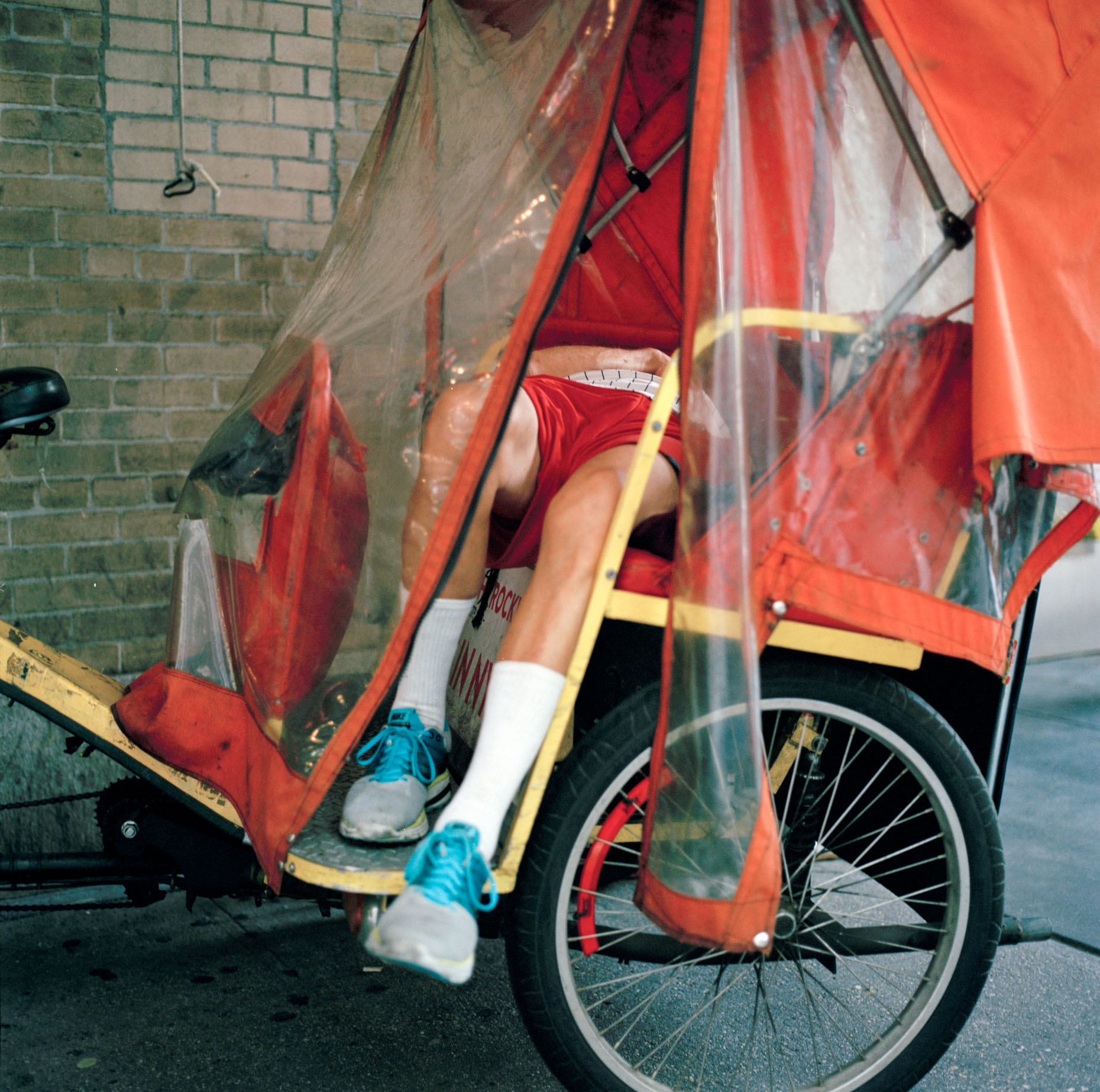 A color film photo of rickshaw rider takes a break on his Rickshaw in the Midtown Summer city heat in New York City,