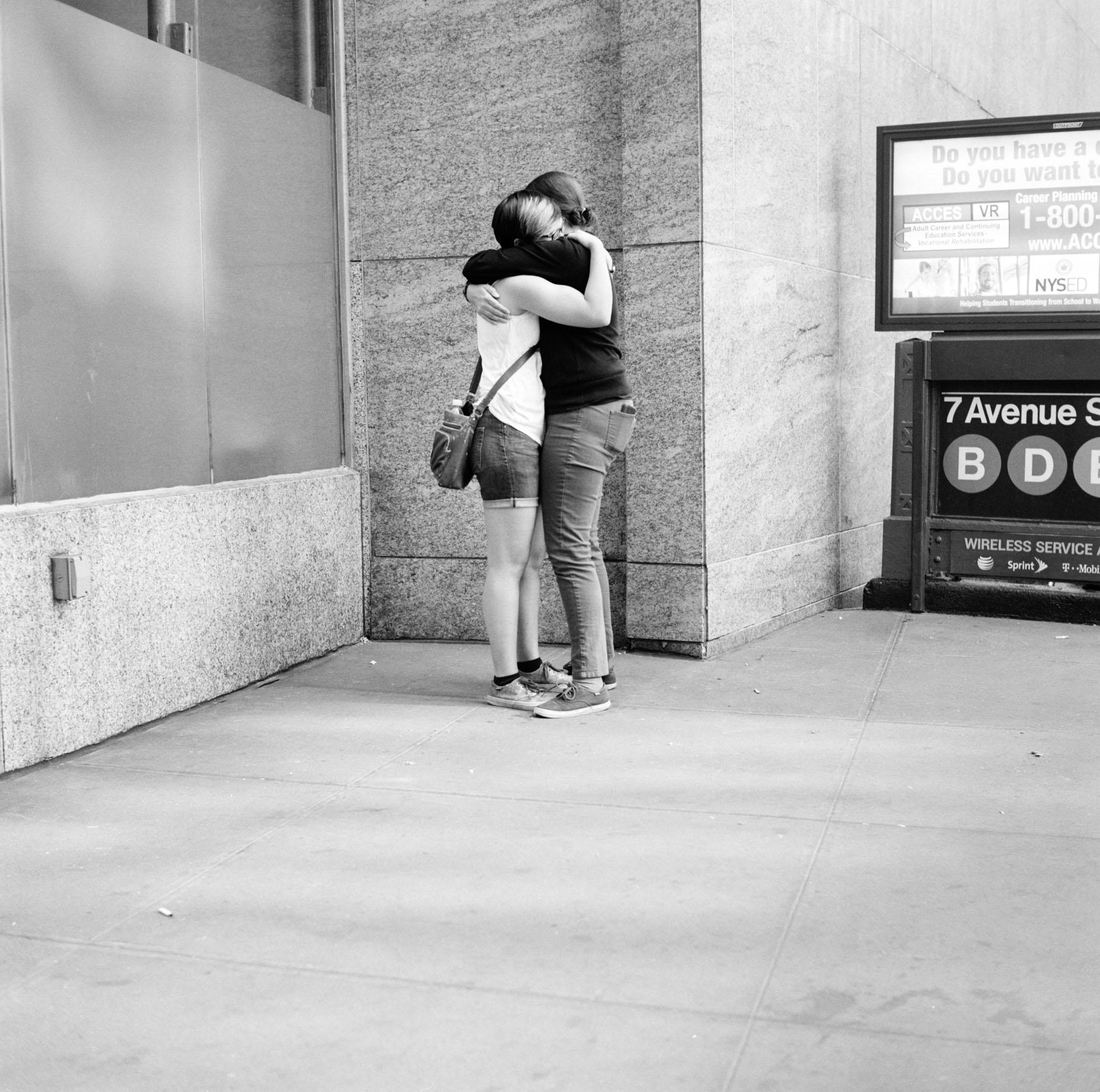 Black and white image of two women embracing  in midtown, New York city.