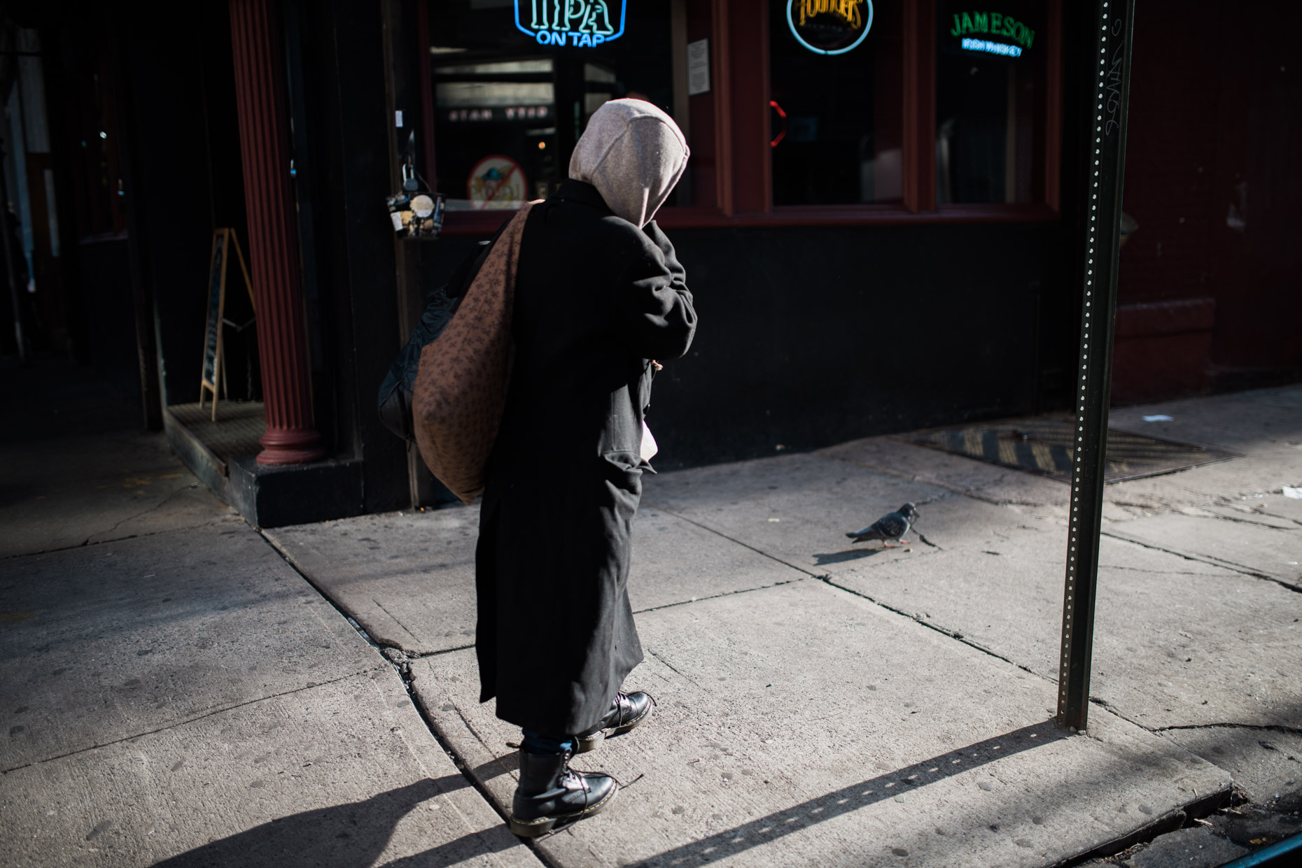 A homeless woman walks past a dive beer and through the Noho area of New York city during a cold and sunny January.