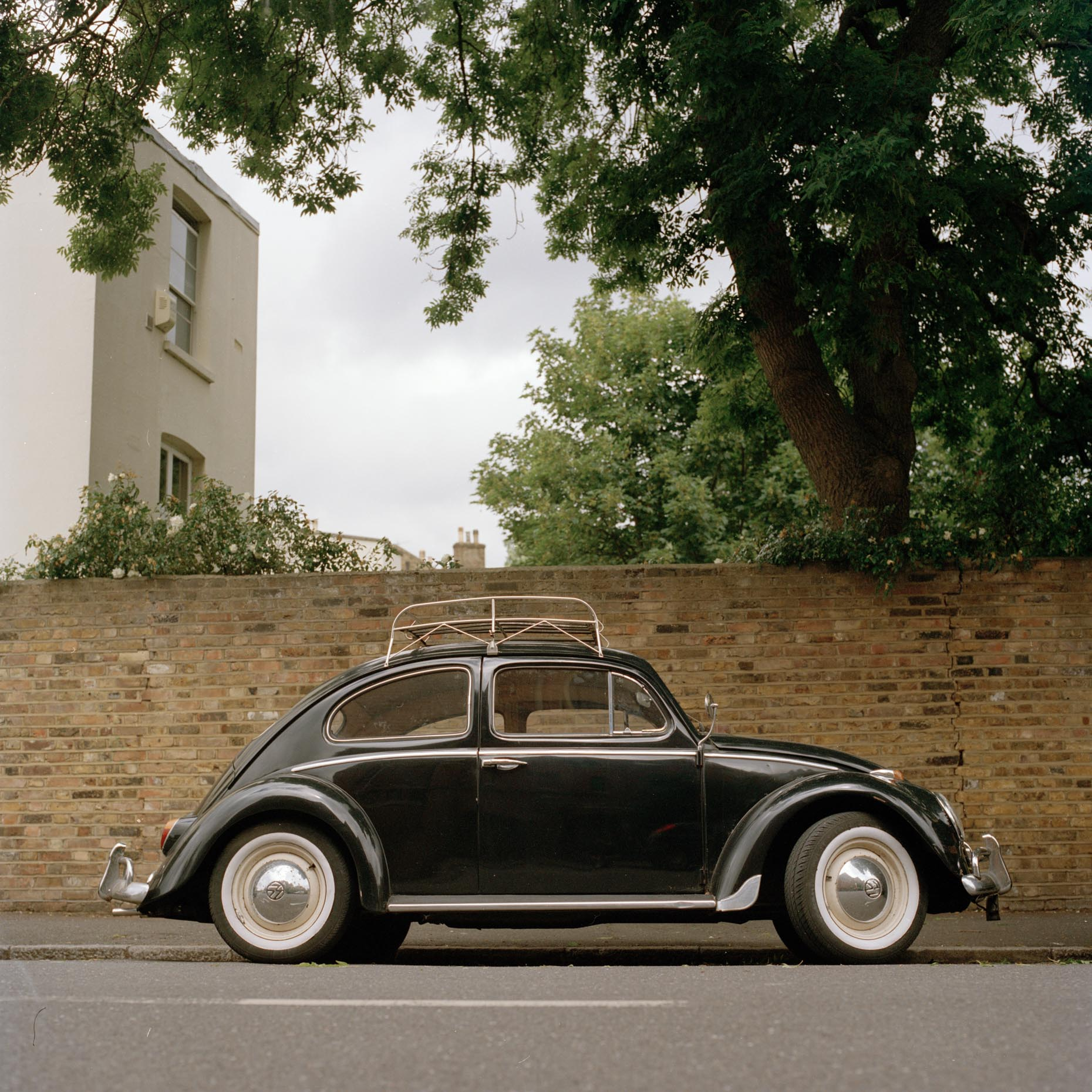 A black volkswagon Beetle sits on a Stoke Newington Street in London, UK.