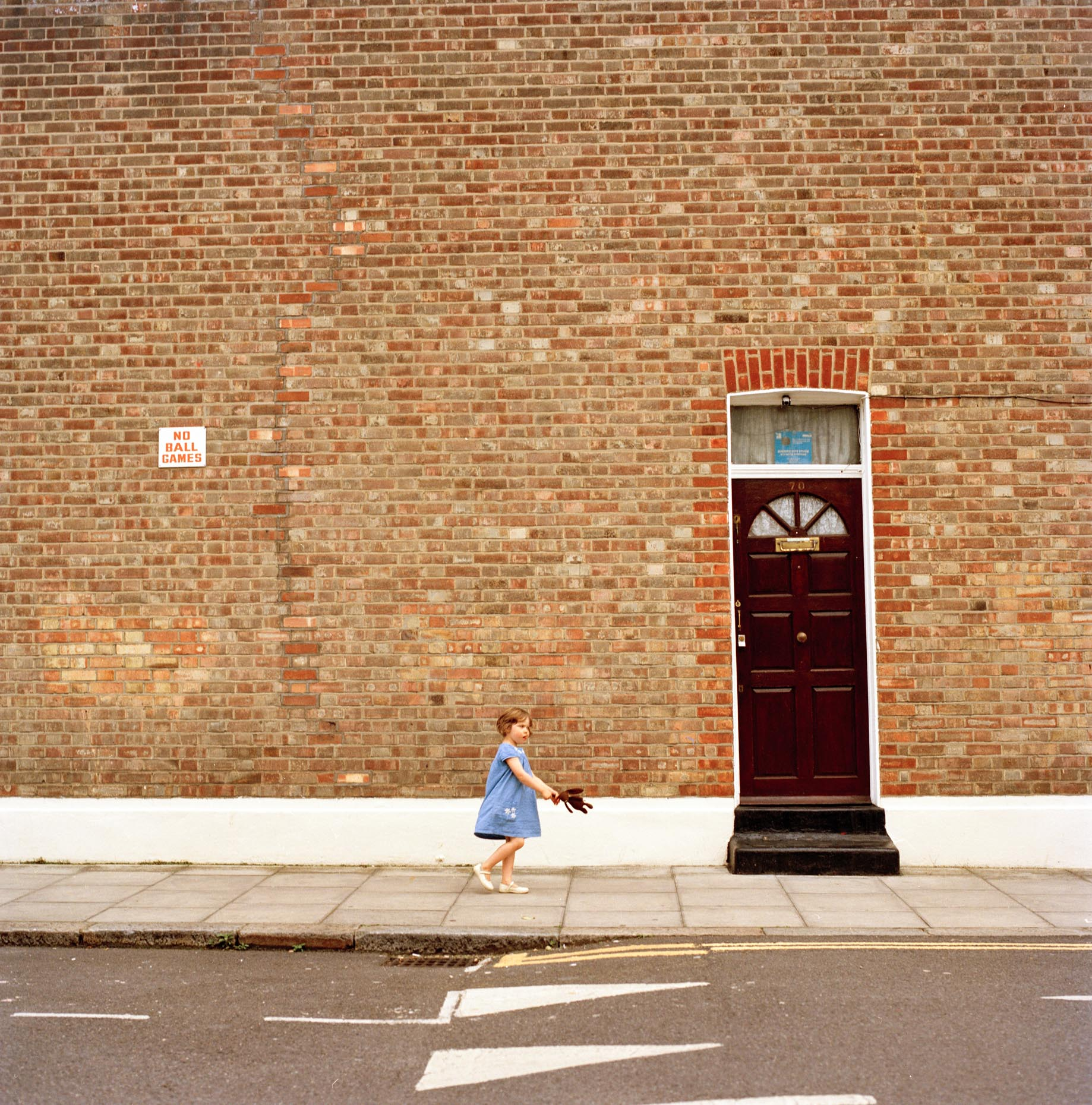 A child swings her toy rabbit while skipping along a North London street in the summer of 2016, UK.