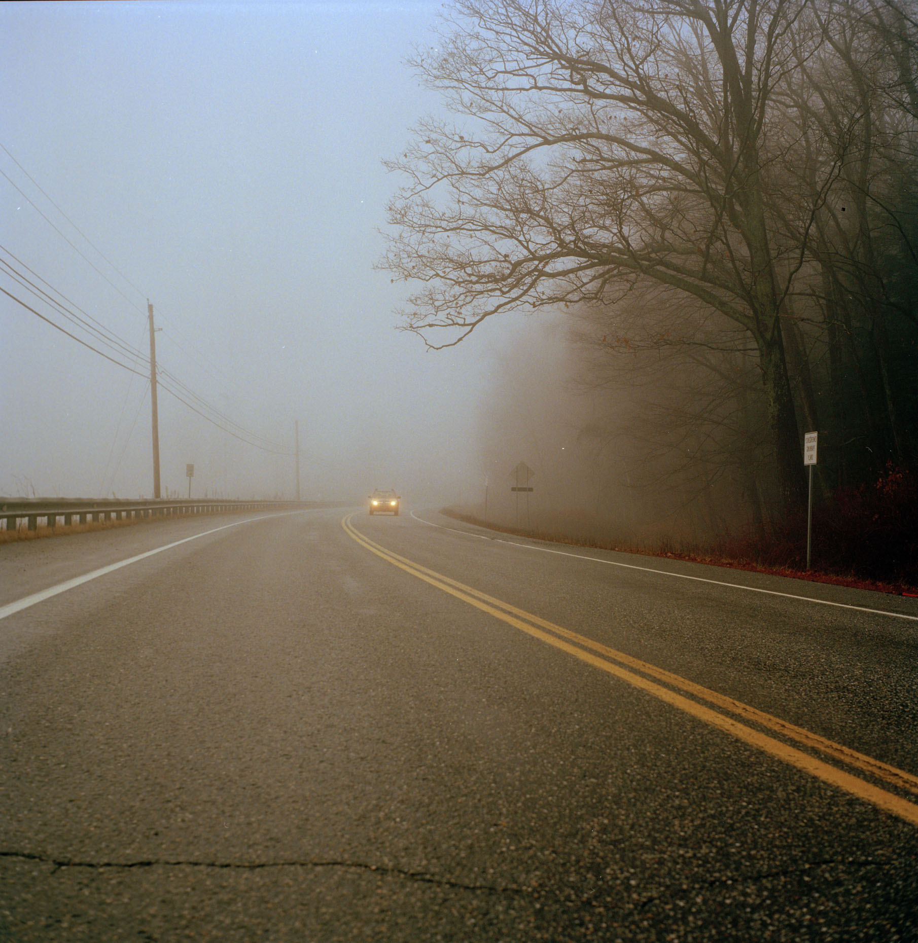 A car drives through the mist and fog through Vermont in the winter of 2015.