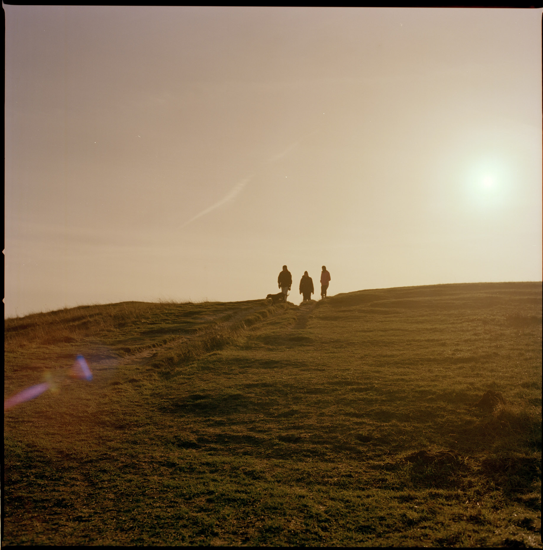 Ramblers bask in the evening sun on the grassy high hills of Ivinghoe Beacon, Buckinghamshire, England.