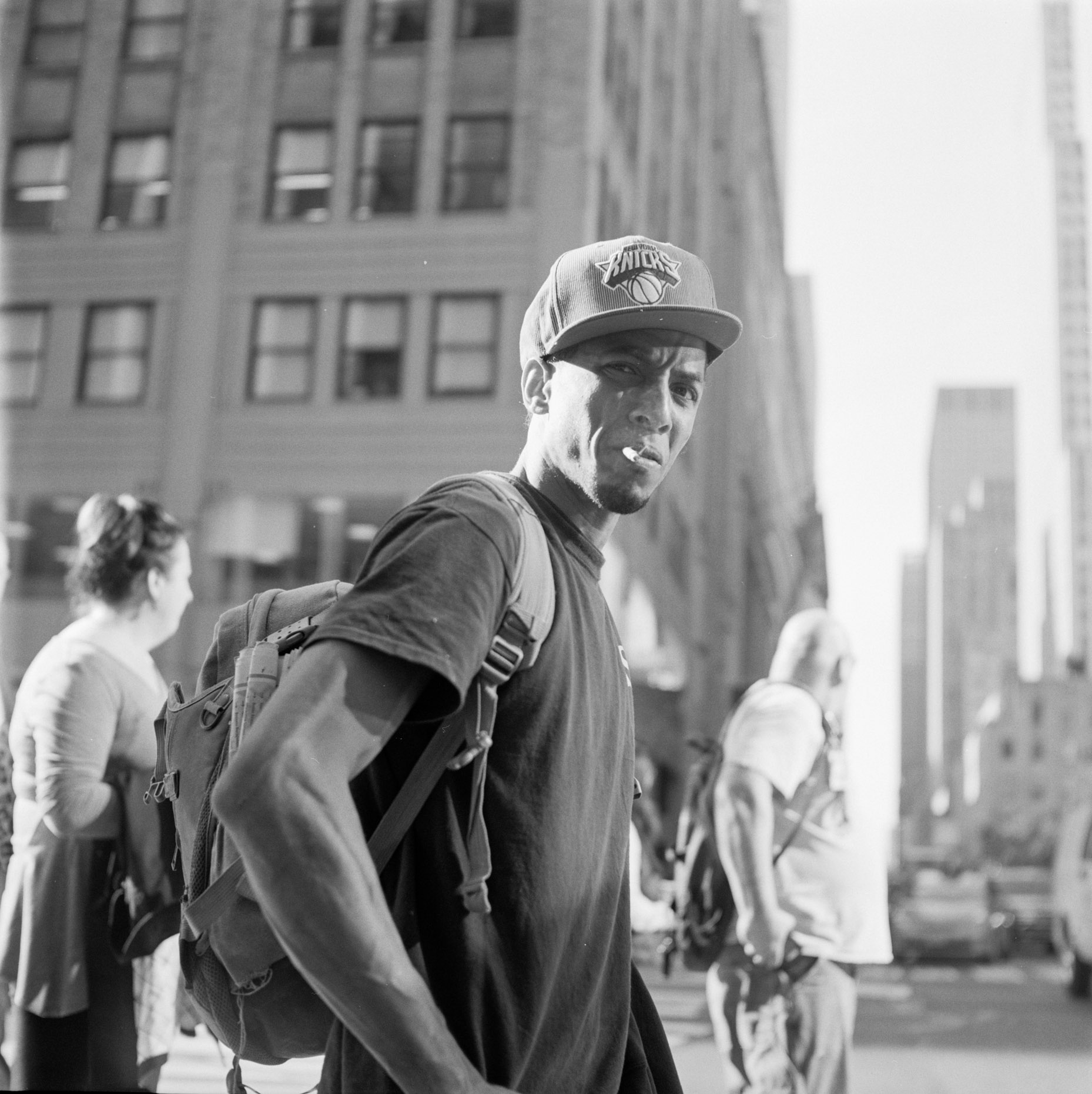 black and white image of young guy walking the streets of Manhattan in New York City