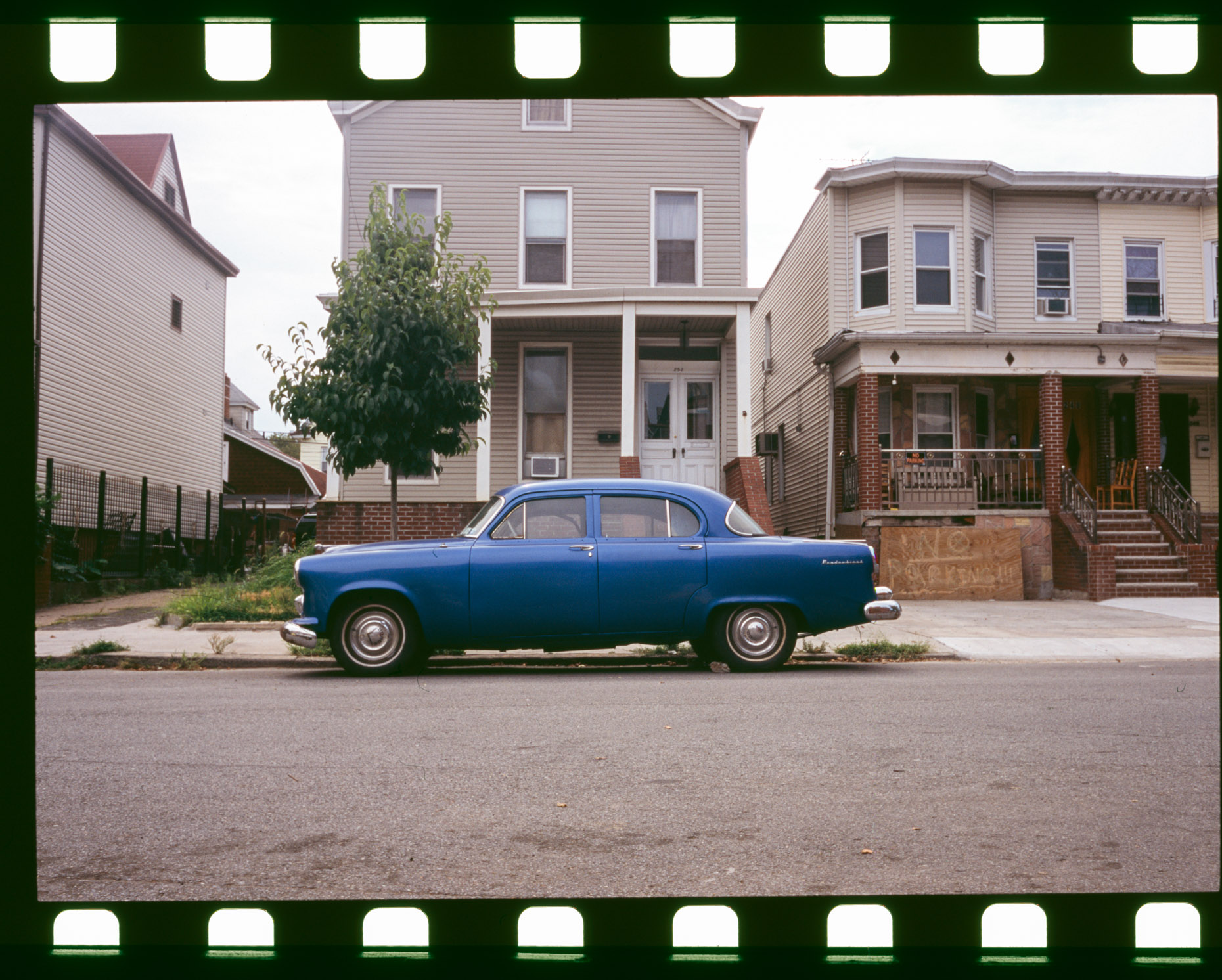 A blue dodge Meadowbrook sits on a suburban street in Kensington, Brooklyn in New York.