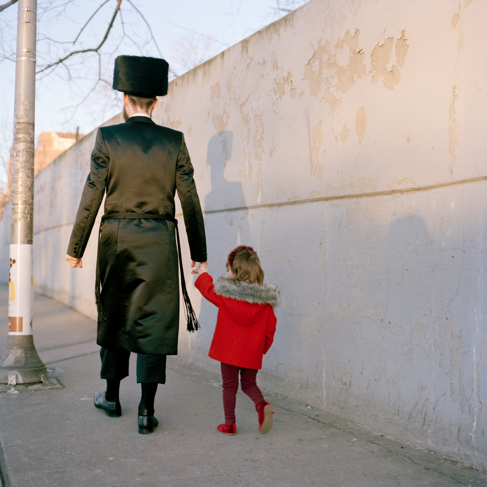 An Orthadox Jewish man holds his daughters hand as he walks through Borough Park, Brooklyn, New York City