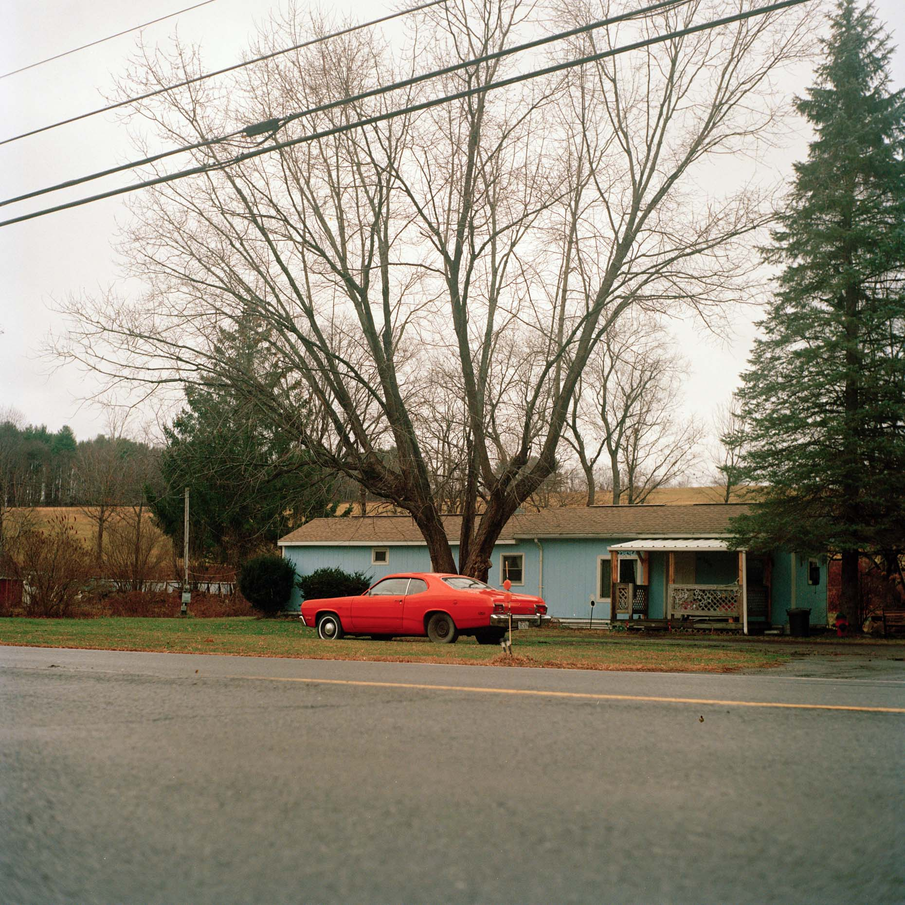 A vintage car sits in the front yard in upstate New York