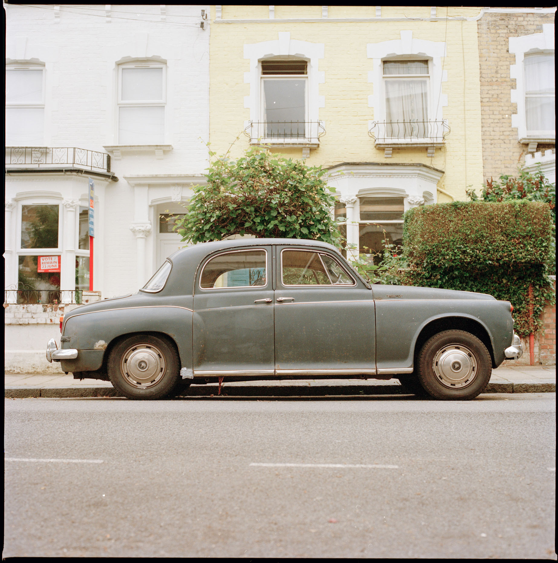 A vintage car sits on a Stoke Newington Street in London, UK.