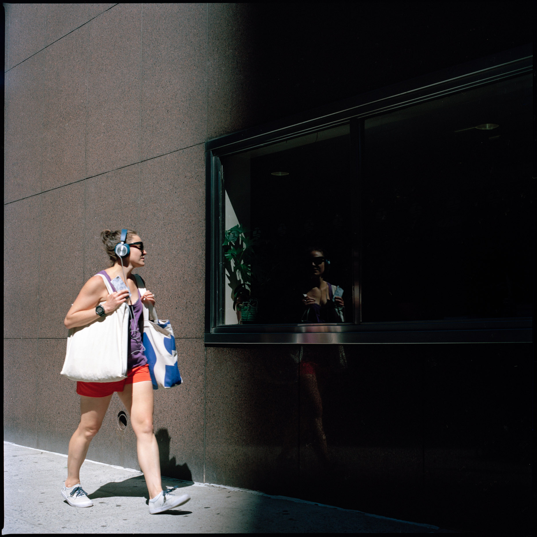A girl catches her reflection while walking in the East village part of Manhattan on a hot weekday afternoon, NYC.