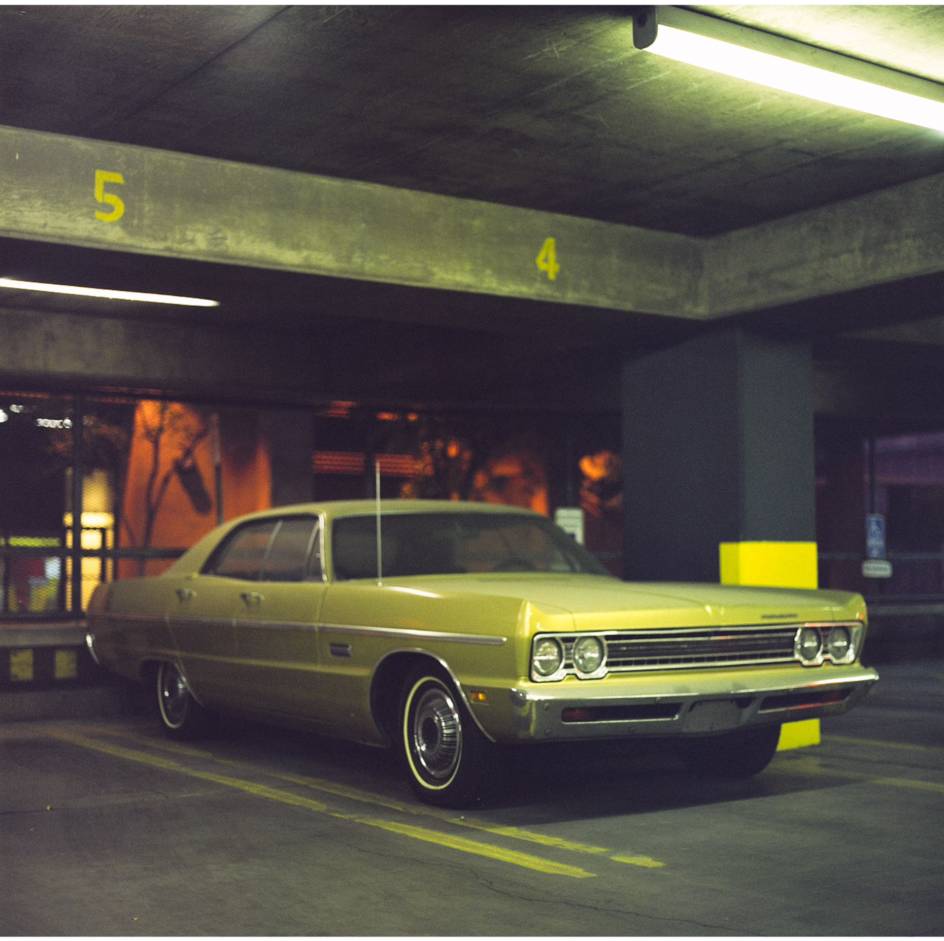 An un-licensed Plymouth Fury sits in a parking lot in  Albuquerque, New Mexico illuminated by the strip lights above.