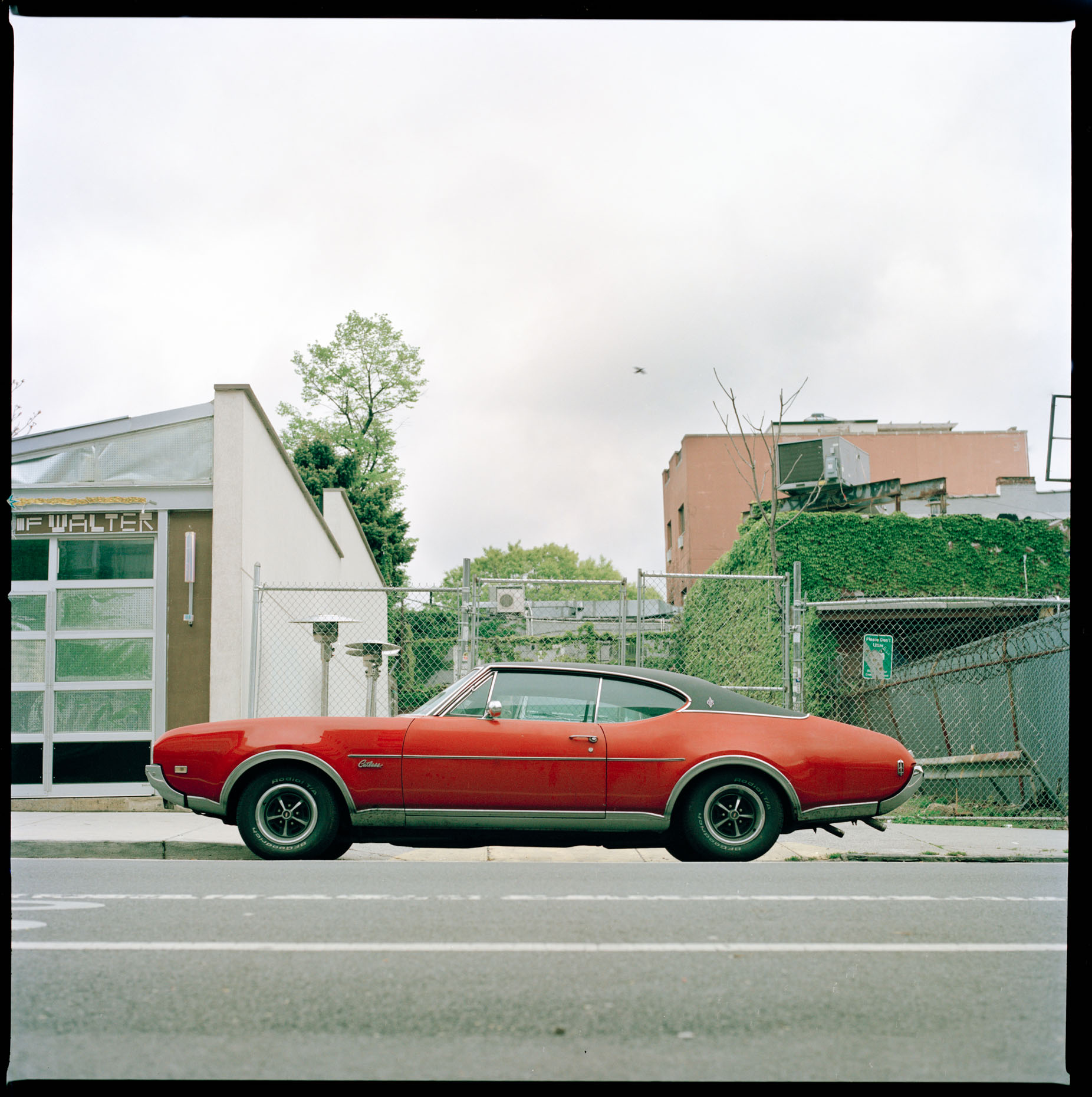 A Red Vitage Oldsmobile Cutlass car sits on a Williamsburg street in Brooklyn, New York.