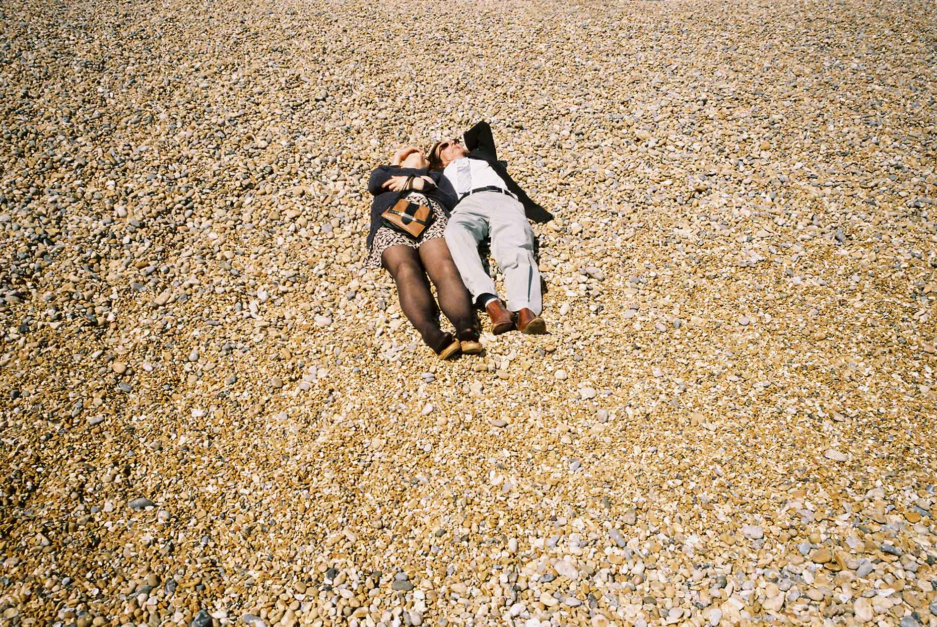 A middle-aged couple take some time out on a sunny day to relax on the pebbled Brighton Beach in the U.K.